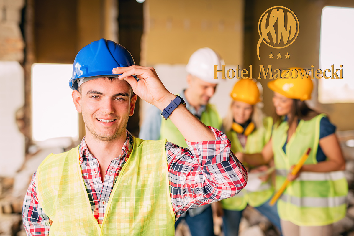 Smiling young electrician holding helmet and looking at camera. His architect colleagues review plan in background at a construction site.